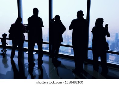 DUBAI, UAE - JAN 23, 2019: Silhouette of people enjoying the view from the 124th floor at Burj Khalifa  during a sunny day. Wide angle showing skyscrapers and the hazy horisont in blue.