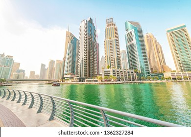 DUBAI, UAE - JAN 24, 2019: Dubai marina with boats and skyscrapers at the canal passing thru the district. Bright pastel colors.