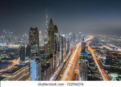 DUBAI, UAE - JAN 8, 2017: Burj Khalifa, Rose Rayhaan by Rotana, Ahmed Abdul Rahim Al Attar Tower at night, Sheikh Zayed highway