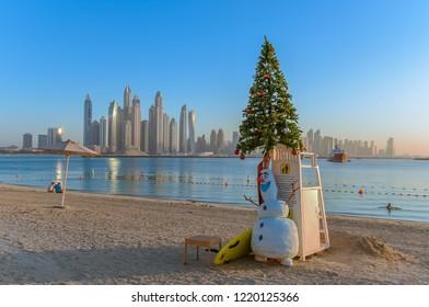 Dubai, UAE - January 1, 2016:  Christmas tree and snowman on a sandy beach overlooking the Dubai Marina skyscrapers