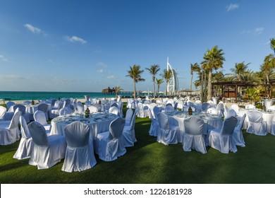 Dubai, UAE - January 10, 2018: Festively decorated banquet tables on the beach overlooking the Hotel Burj Al Arab.