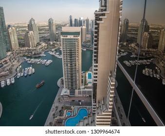 DUBAI, UAE - JANUARY 10, 2019: Dubai Marina's canal and yacht and their reflection in the window.
