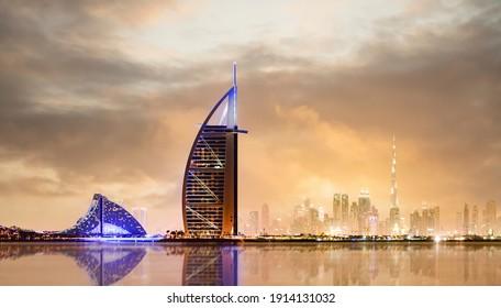 Dubai, UAE, January 10, 2021. Dramatic sunset over the Dubai skyline with the Burj Khalifa in the distance and the Burj al-Arab luxury hotel in the foreground. Dubai, United Arab Emirates.