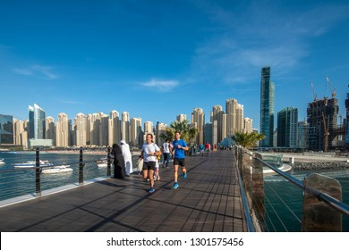 DUBAI, UAE - JANUARY 15, 2019: Two men run along a new pedestrian bridge on Bluewaters Island.