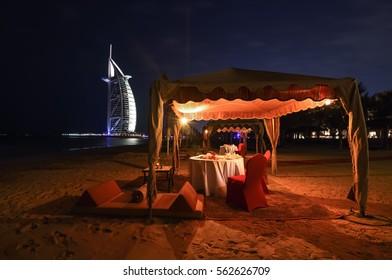 Dubai, UAE - January 16, 2017: A romantic place for dinner on the beach with views of the hotel Burj Al Arab.