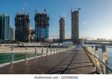 Dubai, UAE - January 16, 2019: Pedestrian Bridge on the Bluewaters Island and construction of new buildings at Jumeirah Beach Residence.
