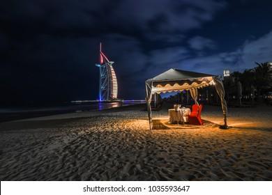 Dubai, UAE - January 17, 2017: Romantic place for dinner on the beach with views of the hotel Burj Al Arab
