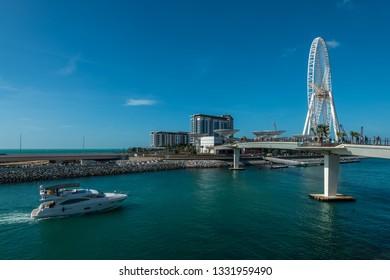 Dubai, UAE - January 18, 2019: Pedestrian bridge over the canal to the Bluewaters Island and Dubai Eye.
