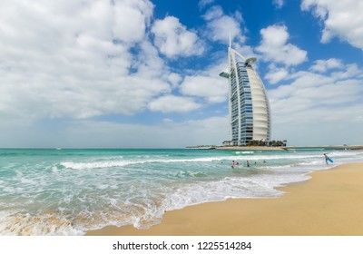 DUBAI, UAE - JANUARY 20, 2018: Young people are swimming on the beach in the background of the Burj Al Arab hotel.