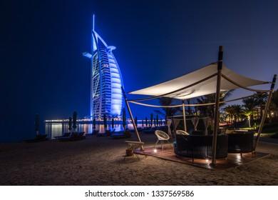 DUBAI, UAE - JANUARY 22, 2018: Modern beach canopy overlooking the Burj Al Arab hotel at night.