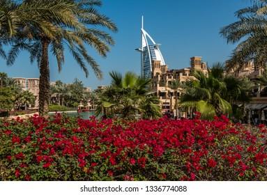 DUBAI, UAE - JANUARY 23, 2019: Hotel Burj Al Arab framed by palm trees and bougainvillea.