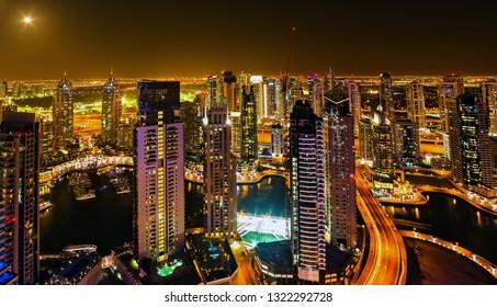 Dubai, UAE - January 24, 2016: Dubai Marina aerial panoramic view on building architecture water pier skyscrapers city by night