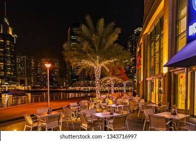 DUBAI, UAE - January 24, 2016: Dubai Marina bay downtown night scene skyscraper reflection city lights restaurant, bars palm trees .