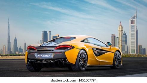 Dubai / UAE - January 29, 2019: Orange McLaren 570S car in Dubai sheikh Zayed road showing Dubai skyline