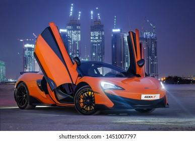 Dubai / UAE - January 29, 2019: Orange McLaren 570S car in Dubai desert showing Dubai Emirate towers