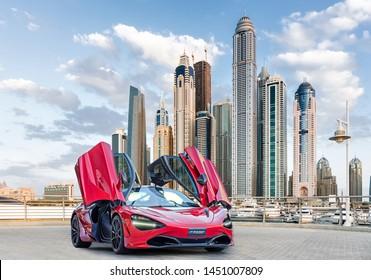 Dubai / UAE - January 29, 2019: Red McLaren 720S car in Dubai Marina showing Dubai Marina towers