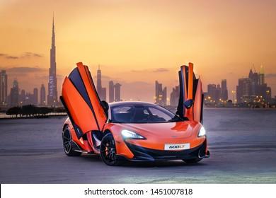 Dubai / UAE - January 29, 2019: Orange McLaren 570S car in Dubai skyline background at the sunset