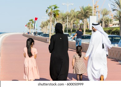 Dubai, UAE, January 5th, 2017, Arabic family wearting traditional drone and walking at the crescent road in the Palm Jumeirah island in Dubai of the United Arab Emirates.