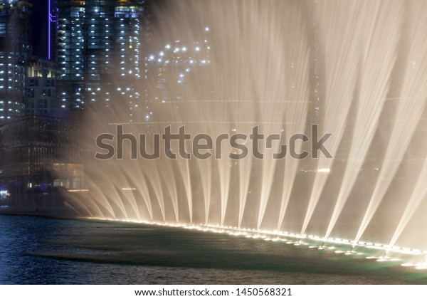 DUBAI, UAE - July 1 2019 : Famous musical fountain in Dubai shopping mall. Dance of the water and water is in the air with great illumination. Lightened water show in artificial lake.