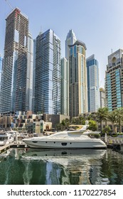 DUBAI, UAE - JULY 14, 2018: Luxury Yacht and Modern skyscrapers in famous Dubai Marina. Marina - artificial canal city, carved along a 3 km stretch of Persian Gulf shoreline.