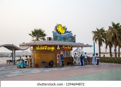 Dubai, UAE - July 20, 2018: People at a restaurant at Jumeirah Public Beach. Jumeira Beach is a white sand beach that is located and named after the Jumeirah district of Dubai.