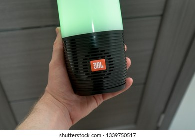 DUBAI, UAE - MARCH 14, 2019: JBL bluetooth speaker close up in the hotel room. Man holds JBL bluetooth speaker in his hand