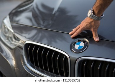 Dubai, UAE - March 20, 2018: BMW sign close up with a man hand and expensive watch. Palm tree reflections on the car surface. Front of BMW 3 Series is shown on the picture