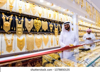 Dubai, UAE, March 2019 - A jewelry reseller at work in a shop at the Dubai Gold Souk market, United Arab Emirates