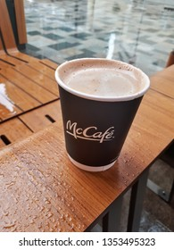 Dubai, UAE - March 28, 2019: Paper take away black cup with hot fresh Arabic karak tea from McCafe McDonald's during the rain in Dubai.  Cup is on the wooden wet surface