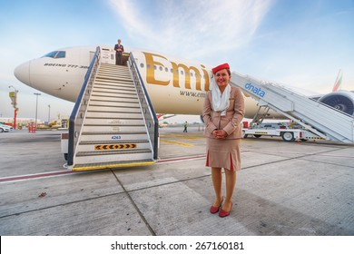 DUBAI, UAE - MARCH 31, 2015: Emirates crew member near Boeing-777. Emirates is one of two flag carriers of the United Arab Emirates along with Etihad Airways and is based in Dubai.