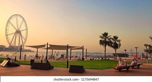 Dubai, UAE - May 08, 2018: Dubai Marina promenade at sunset. Ferris wheel, Dubai marina beach, United Arab Emirates.  Marina is a district with artificial canal city,