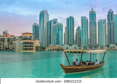 Dubai, UAE - May 1, 2013: tourists take a boat ride near Dubai fountain show area, Dubai Mall and Burj Khalifa, in front of Souk Al Bahar. On background, the skyscrapers of Old Town Island at sunset.