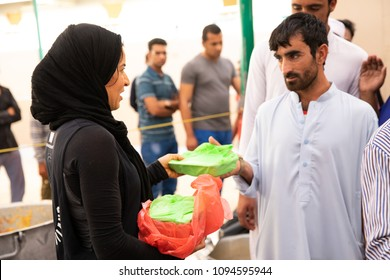 Dubai, UAE - May 18, 2018: Volunteers distributing food packages to workers during iftar meal as part of a Ramadan charity drive by local mosque.