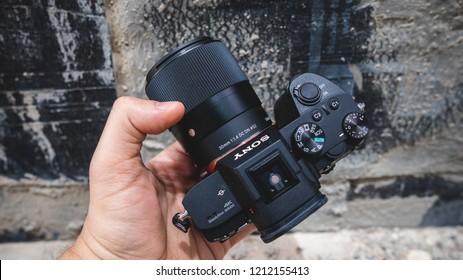 Dubai, UAE - May 2018 : A hand holding Sony A7 iii Mirrorless Camera with Sigma 30mm f1.4 DC DN