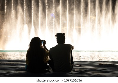 Dubai, UAE - May 25, 2018: A couple watching the light and water show of Dubai Mall fountains from a floating platform after dark.
