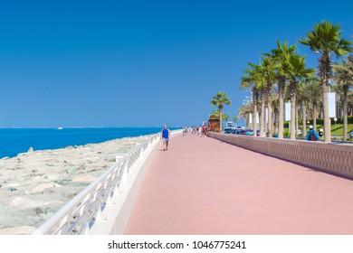Dubai, UAE - November 03, 2017:Boardwalk along the sea on palm island in Dubai. Clear blue sky over Dubai coastline.