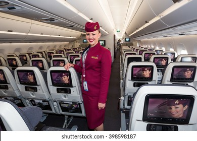 Dubai, UAE - NOVEMBER 08, 2015: Qatar Airways Airbus A350 cabin crew member, flight attendant. Qatar Airways stewardess. Qatar Airways economy class seats.