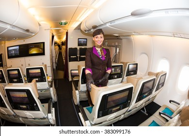 Dubai, UAE - NOVEMBER 09, 2015: Etihad Airways flight attendant, cabin crew member. Etihad Airways economy class seats. Etihad stewardess. Etihad Airways Airbus A380 on November 09, 2015 in Dubai