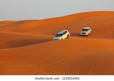 DUBAI, UAE - November 09, 2018: Off-road adventure with SUVs driving in Arabian Desert at sunset. Traditional entertainment for tourists with vehicle bashing through sand dunes in Dubai desert.