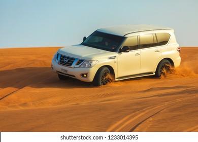 DUBAI, UAE - November 09, 2018: Off-road adventure with SUV in Arabian Desert at sunset. Offroad vehicle bashing through sand dunes in Dubai desert.