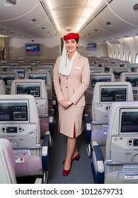 Dubai, UAE - NOVEMBER 12, 2017: Emirates beautiful flight attendant. Emirates Airline Airbus A380 travel. Stewardess dress. Flight attendant portrait. In flight entertainment system.