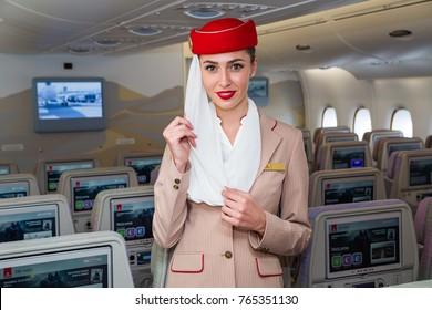 Dubai, UAE - NOVEMBER 12, 2017: Emirates beautiful flight attendant. Emirates Airbus A380 travel. Stewardess dress. Flight attendant portrait. Emirates airline travel. IFE system. Economy class seats.