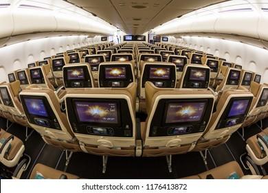 Dubai, UAE - NOVEMBER 13, 2017: Etihad Airways economy class seats. Airbus A380 cabin. Inflight entertainment system IFE screens. Travelling with Etihad Airways.