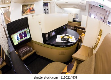 Dubai, UAE - NOVEMBER 13, 2017: Etihad Airways business class luxury seats. Business class seat. Airbus A380. Travelling with Etihad airways. Luxury travel. Inflight entertainment system IFE screen.