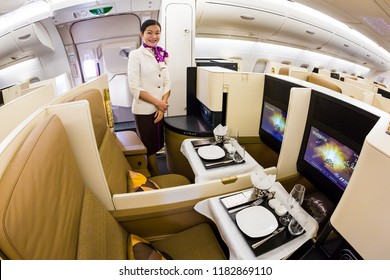 Dubai, UAE - NOVEMBER 13, 2017: Etihad Airways business class luxury seats. Business class seat. Airbus A380. Onboard dining. Luxury travel. Travelling with Etihad Airways. Flight attendant portrait.