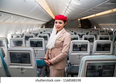 Dubai, UAE - NOVEMBER 14, 2017: Emirates airline flight attendant. Cabin crew member. Boeing 777. Travelling with Emirates. Best airline. Dubai airport. Inflight entertainment system IFE screen.
