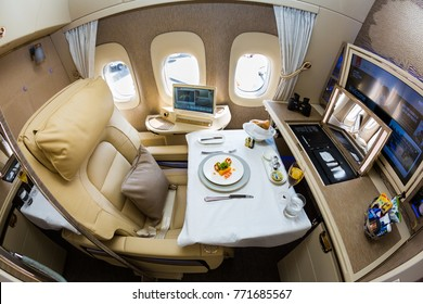 Dubai, UAE - NOVEMBER 14, 2017: Emirates new first class suite. Emirates luxury travel. Boeing 777. Onboard dining, food. Renewed first class cabin. Brand new design. First class seat.
