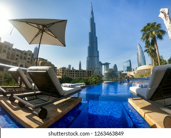 Dubai, UAE - NOVEMBER 15, 2018: Dubai pool view. Best Dubai view. Futuristic city. Burj Khalifa tallest building in the world. Dubai resort, holiday, relax. Hotel pool. Sunbeds and infinity pool.