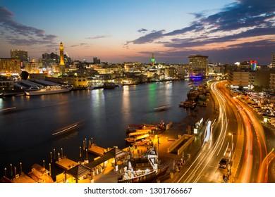 Dubai, UAE - NOVEMBER 20, 2018: Deira historic district of Dubai. Night city. Sunset sky. Dubai skyline. Tourist destination. Old city. Dubai creek. Abra boats. City lights, night roads.
