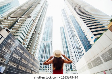 DUBAI, UAE - NOVEMBER 2018: Back view of young woman in red summer dress holding with both hands straw hat looking up on skycrapers at downtown of modern city.